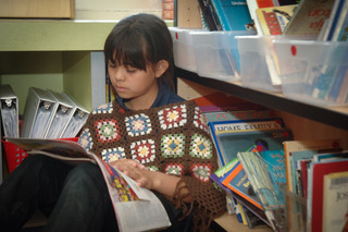 Student reads a book in the library